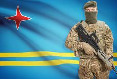 Soldier holding machine gun with national flag on background - Aruba Stock Photos