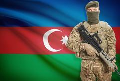Soldier holding machine gun with national flag on background - Azerbaijan - stock photo