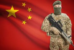 Soldier holding machine gun with national flag on background - People's Repub Stock Photos