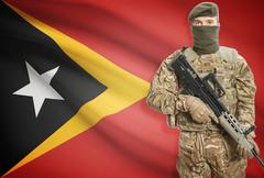 Soldier holding machine gun with national flag on background - East Timor - stock photo