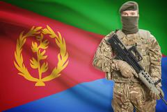 Soldier holding machine gun with national flag on background - Eritrea - stock photo
