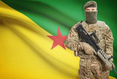 Soldier holding machine gun with national flag on background - French Guiana - stock photo