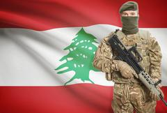 Soldier holding machine gun with national flag on background - Lebanon - stock photo