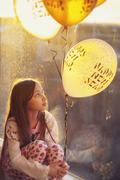 Girl sitting by a window Holding New Years Eve Balloons Stock Photos