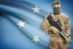 Soldier holding machine gun with national flag on background - Micronesia - stock photo