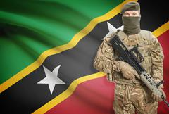 Stock Photo of Soldier holding machine gun with national flag on background - Saint Kitts an