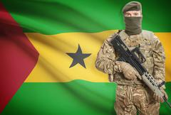 Soldier holding machine gun with national flag on background - Sao Tome and P Stock Photos