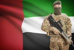 Soldier holding machine gun with national flag on background - United Arab Em - stock photo