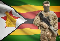 Soldier holding machine gun with national flag on background - Zimbabwe - stock photo