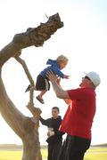 Father catching son jumping off a tree trunk with boy in background - stock photo