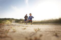 Low angle view of Two boys running in countryside Kuvituskuvat