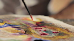 Painting with orange color over a watercolor portrait Stock Footage