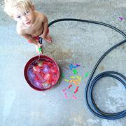 Toddler filling a bucket with water Stock Photos