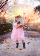 Girl standing in road playing the violin with leaves falling all around - stock photo