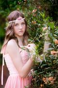Girl in a headdress in the garden - stock photo