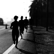 Silhouette of people running a Marathon - stock photo