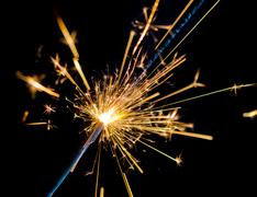 close-up of firework sparkler burning on black background, congratulation gre - stock photo