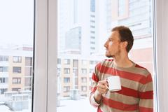 Handsom man standing by the window having coffee and looking on the citiy Stock Photos