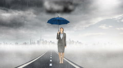 Composite image of businesswoman holding an umbrella - stock footage