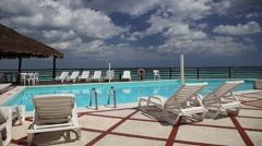 Lounge sunbeds near swimming pool Stock Footage
