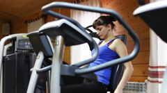 Woman in a fitness room on an exercise bike Stock Footage