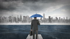 Composite image of businessman holding an umbrella - stock footage