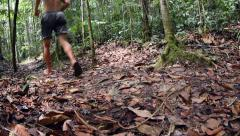 Wide low angle slow motion man running on Amazon jungle trail Stock Footage