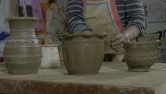 In foreground products of clay,in background man making vase, pottery, close up. - stock footage