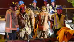 Firefighters working on getting trapped victim out of car Stock Footage