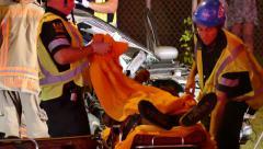 Paramedic puts Blanket on Victim on gurney after car Crash - stock footage