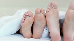 Two pairs of feet in bed crossing over each over - stock footage