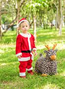 Asian baby boy in santa claus suit is playing with reindeer doll  at the park - stock photo