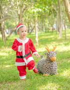 Asian baby boy in santa claus suit is playing with reindeer doll  at the park Stock Photos