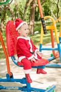 Asian baby boy in santa claus suit is playing  at the park - stock photo