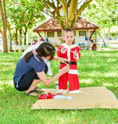 Young Asian mother wearing santa cluas suit to her son, family scene Stock Photos