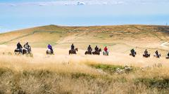 Horsemen proceed in single file through high grass. - stock photo