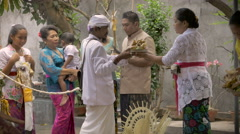 Wide shot of a ceremony group receiving blessings from a Hindu priest in Bali - stock footage