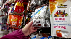 Woman selecting chocolate in grocery store Stock Footage