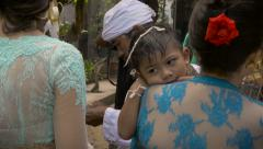A woman holds a young tired boy during a Hindu ceremony - stock footage