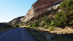 POV -Driving desert road morning light passing rocky cliff, cottonwood & juniper Stock Footage