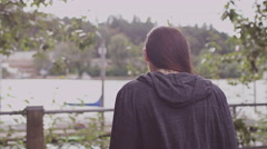 A beautiful girl walking toward a waterfront looks back to the camera Stock Footage