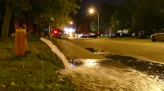 Lots of water flowing out of hydrant on residential street Stock Footage