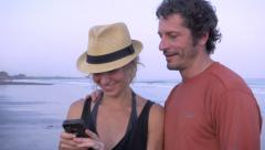 Hand held couple on cell phone at the beach Stock Footage