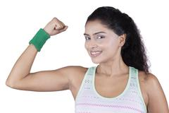 Cheerful woman showing her bicep - stock photo