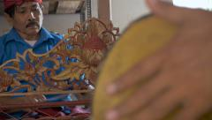 Balinese musicians play a xylophone and hand drum during a ceremony Stock Footage