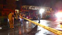 Firefighter putting out Yellow do not cross Tape Stock Footage