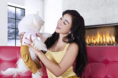 Happy woman smiling at her dog at home - stock photo