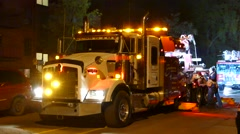 Men operating large brightly lit tow truck at night - stock footage
