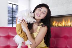 Lovely girl hugging her puppy on couch - stock photo