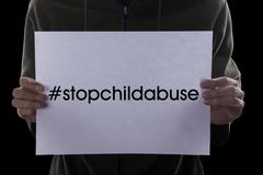 Man holds text of stop child abuse - stock photo